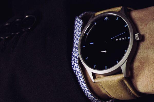 Mann im dunklen Anzug mit minimalistischer Uhr