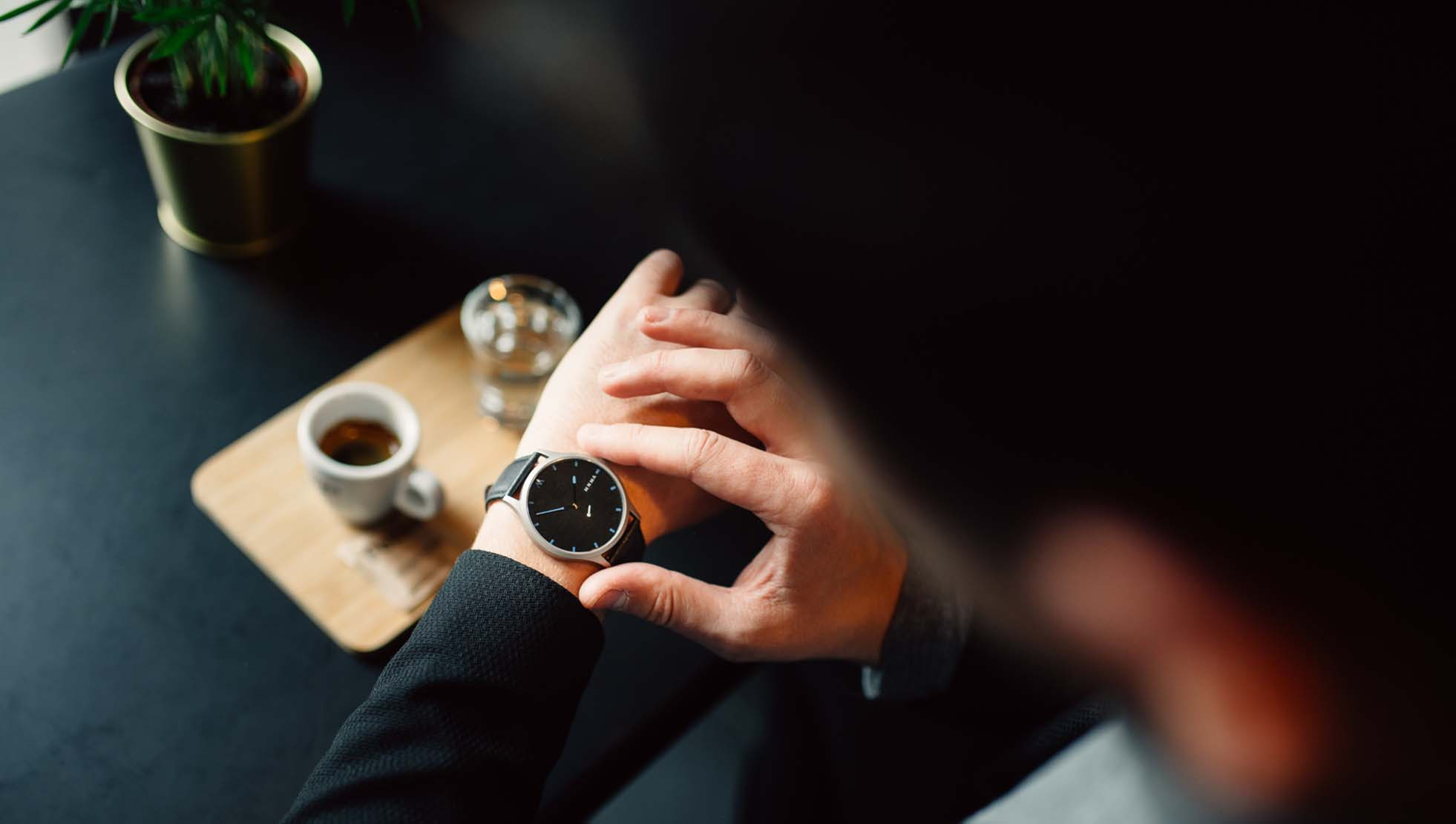 Man drinking espresso and looking what time it is