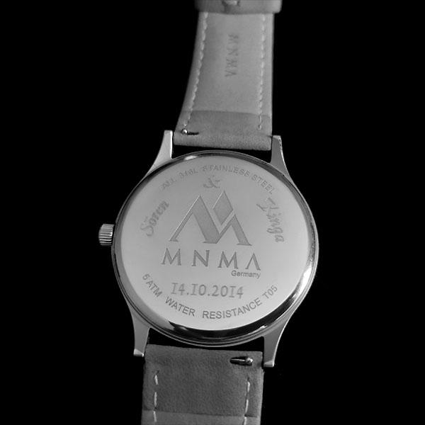 Uhr mit Gravur von MNMA auf Rückseite