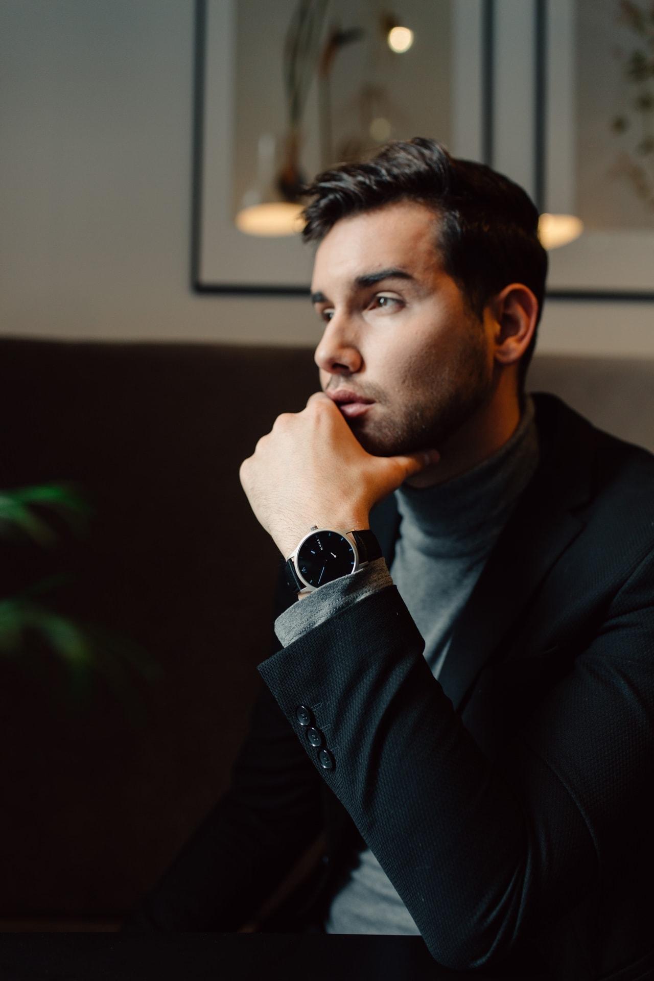 Mann der eine dunkle Herrenuhr trägt zum eleganten Outfti